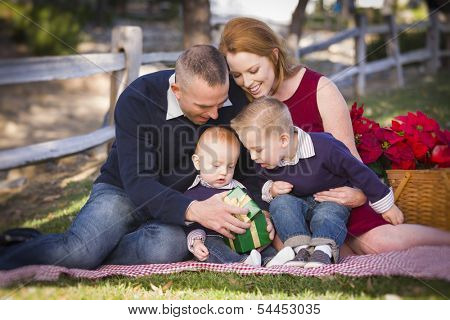 Beautiful Small Young Family Opening Christmas Gifts in the Park.