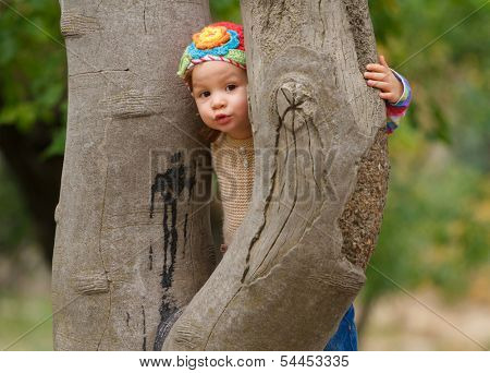 Sweet toddler girl hiding behind the tree