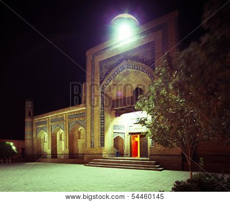Oriental building with trees on the yard at night.The city of Khiva, Uzbekistan