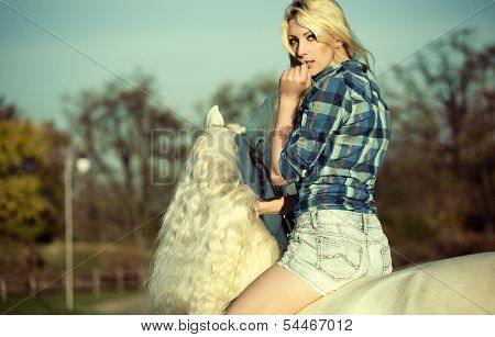 Portrait of young beautiful woman riding horse