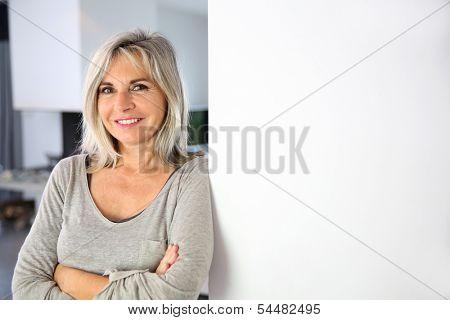 Senior woman standing against white wall