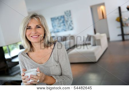 50-year-old woman at home drinking tea