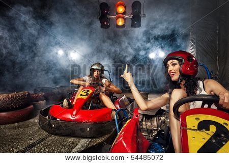 girl is driving Go-kart with speed in Karting. Aggressive woman indicating finger