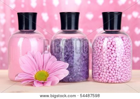 Aromatherapy minerals - colorful bath salt on pink background
