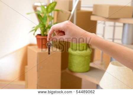 Female hand with keys ob stack of cartons background: moving house concept