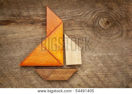 abstract picture of a sailing boat built from seven tangram wooden pieces over a rustic  barn wood, artwork created by the photographer