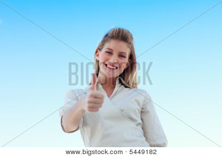 Businesswoman Smiling At The Camera With Thumb Up Against Blue Sky