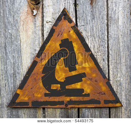 Microscope Icon on Weathered Warning Sign.