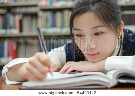 Tired Student Doing Homework In Library