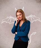 stock photo of nasty  - Young nasty girl with devil horns and wings drawing - JPG