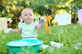 image of wash-basin  - The little girl washes clothes in a small green basin near the rope with drying clothes - JPG