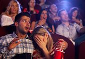image of cinema auditorium  - Young couple watching horror movie in cinema - JPG