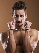 foto of handcuffed  - Handsome young man arrested with handcufs on his hands - JPG