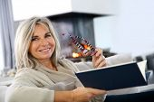 stock photo of single woman  - Senior woman reading book at home by fireplace - JPG