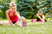 stock photo of cardiovascular  - Portait of a blond girl getting streching her legs before running outdoors - JPG