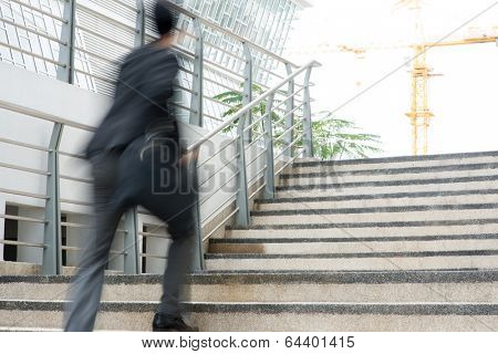 Businessman in hurry. Motion blurred people over office building.
