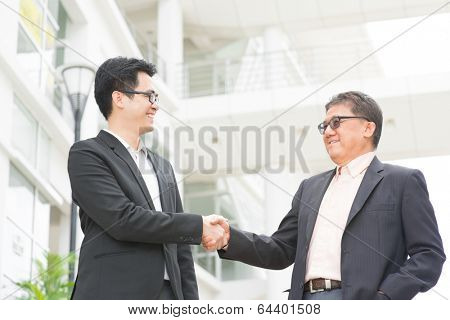 Asian businessmen handshaking. Senior CEO hand shake with young executive. Modern  office building architecture background.