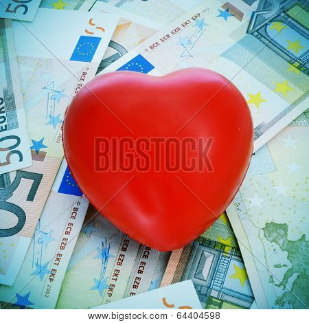 a red heart on a pile euro banknotes depicting the idea of love for the money or the cost of love or the cost of the cardiovascular diseases for the healthcare system