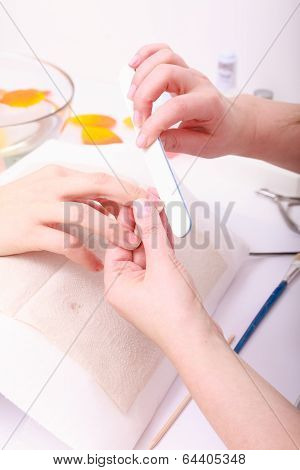 Beautician With File Filing Nails Female Client. Woman Spa Beauty Salon