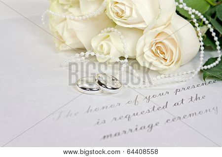 white wedding roses and rings