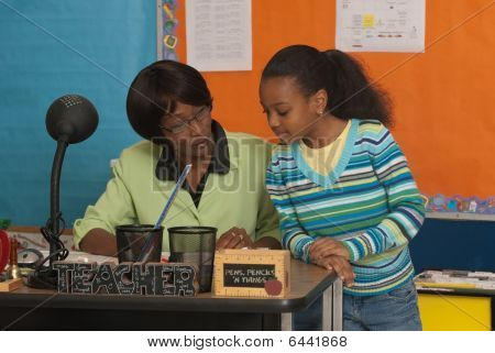 Student an Lehrer Schreibtisch