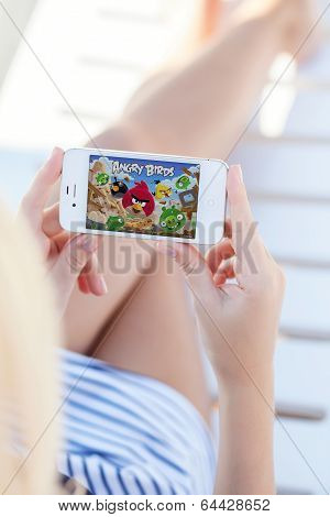 Girl Lying On A Chaise Lounge Holding Iphone With Game Angry Birds On The Screen