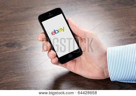 Businessman Holding Iphone With Ebay On The Screen Over The Villages Table