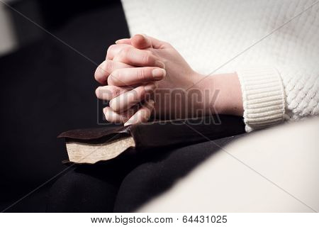 Praying woman folding hands over bible