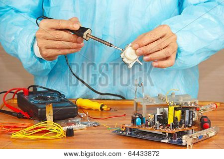 Serviceman solder electronic hardware in service workshop