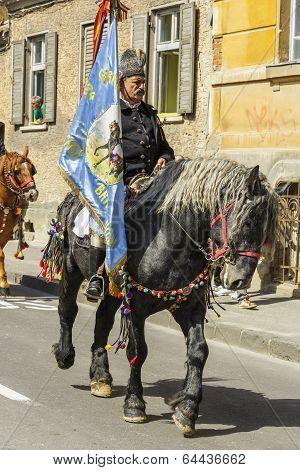 Senior Horseman Holding Flag During Brasov Juni Parade