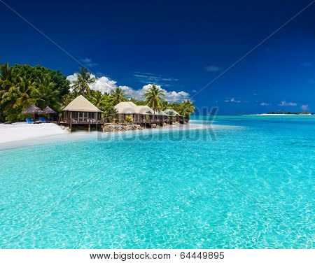 Beach Villas on small tropical island with palm trees