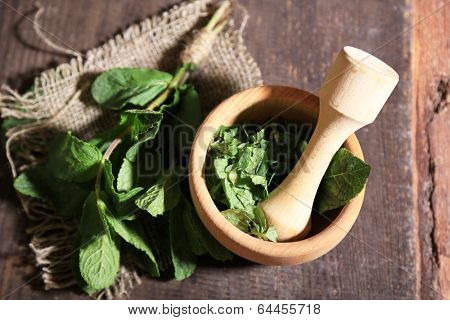 Composition with wooden mortar and mint leaves on  color wooden background