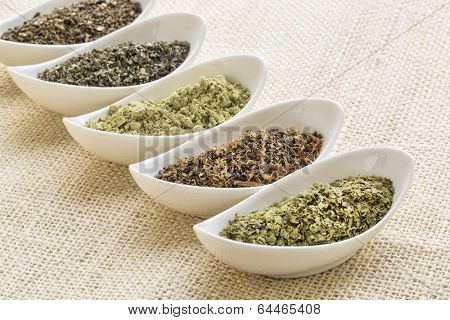 bowls of seaweed diet supplements (bladderwrack, sea lettuce, kelp, wakame and Irish moss) on burlap canvas