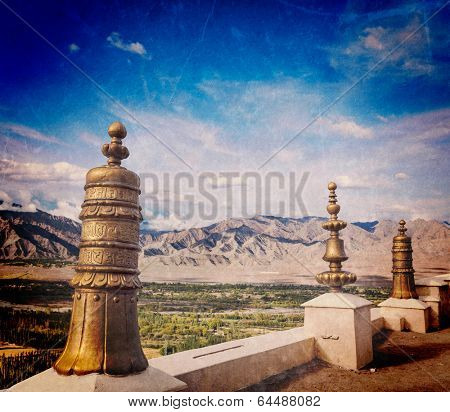 Vintage retro effect filtered hipster style travel image of Dhvaja victory banners on roof of Thiksey gompa (Tibetan BUddhistm monastery) and view of Indus valley with grunge texture. Ladakh, India