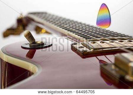 Close Up Of A Red Electric Guitar With Flying Rainbow Pick