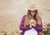 picture of girl walking away  - Teenage hipster girl enjoying her take away drink walking down the city street - JPG