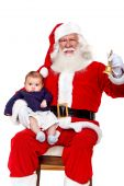 stock photo of santa-claus  - Santa with a baby ringing his bell isolated on white - JPG