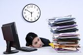 stock photo of piles  - Portrait of overworked businesswoman looking at pile of documents - JPG