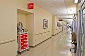 stock photo of defibrillator  - Emergency code cart in recess of corridor of modern hospital - JPG