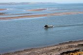 picture of lobster boat  - Lobster or creel fishing boat returning to port along river estuary - JPG
