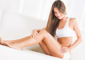 pic of body-lotion  - Beautiful young woman applying body lotion at home - JPG
