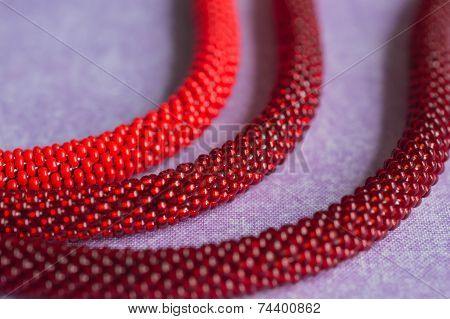 Necklace From Beads Of Three Shades Red On A Textile Background