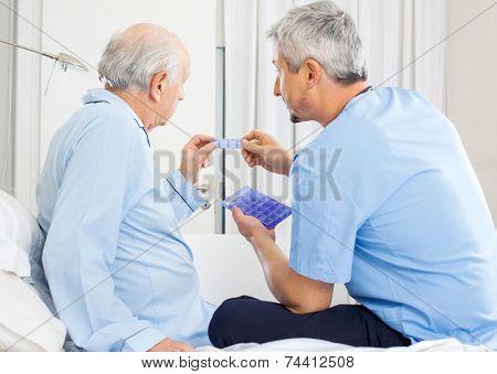 Male caretaker guiding prescription to senior man in bedroom at nursing home
