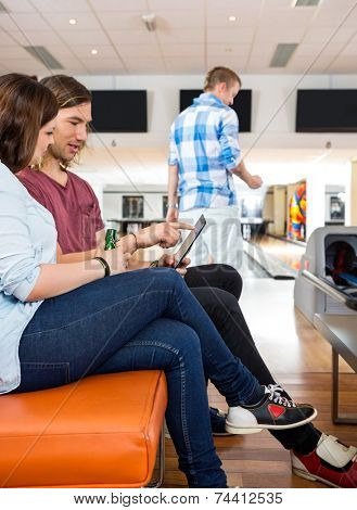 Side view of young man and woman using digital tablet on couch in bowling club