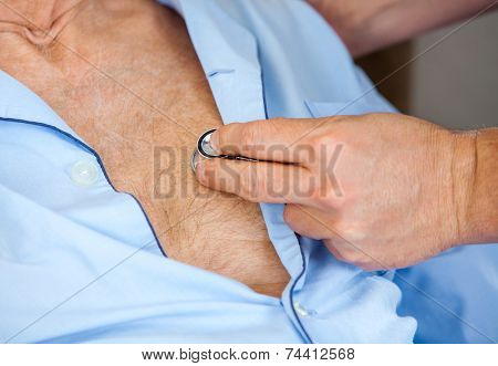 Cropped image of male caretaker examining senior man's chest with stethoscope at nursing home