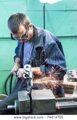 Senior worker grinds detail