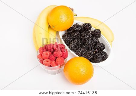 Oranges Raspberries Blackberries And Bananas On White