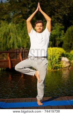 Young man practicing yoga, doing tree pose