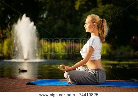 Young woman maditating in lotus pose