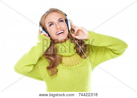 Happy woman enjoying her music looking up into the air and laughing as she listens to tunes on her headphones  isolated on white